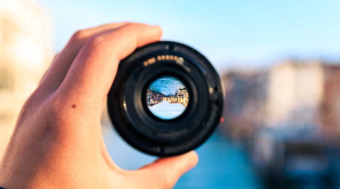 Obiektyw aparatu w dłoni