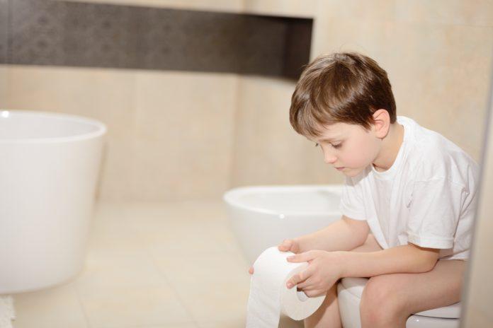 Chłopiec siedzący na toalecie z papierem toaletowym w rękach