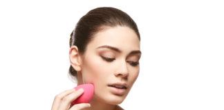 Kobieta używająca różowej gąbeczki do makijażu