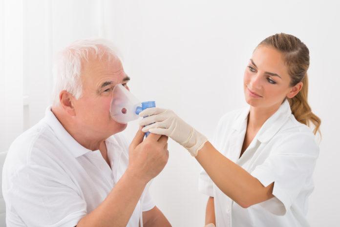 mężczyzna oddychający dzięki inhalatorowi