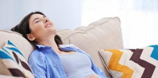 Kobieta ubrana na niebiesko cierpiąca z powodu wzdęć brzucha
