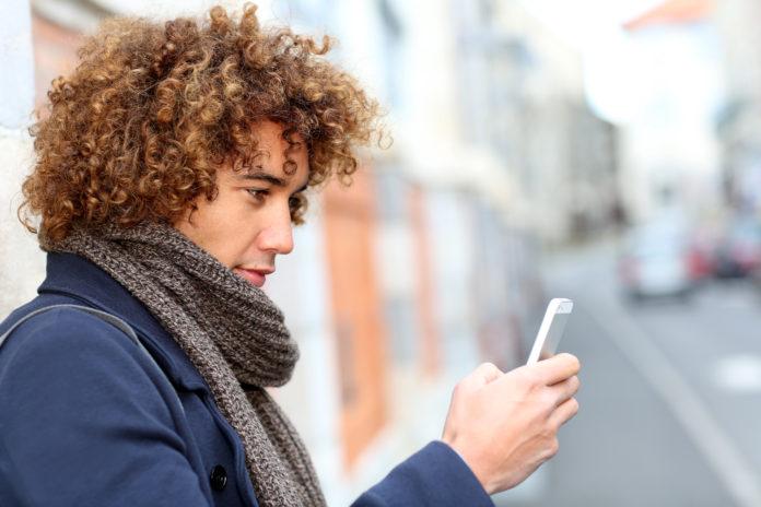 chłopak z lokami na głowie wpatrzony w smartfon