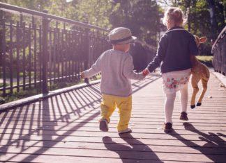 dzieci idące za rękę ubrane w stylu casual