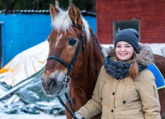 uśmiechnięta dziewczyna z koniem zimą