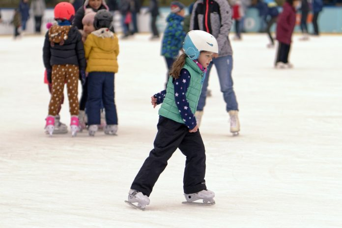 Dziewczynka jeżdżąca na łyżwach w kasku na lodowisku