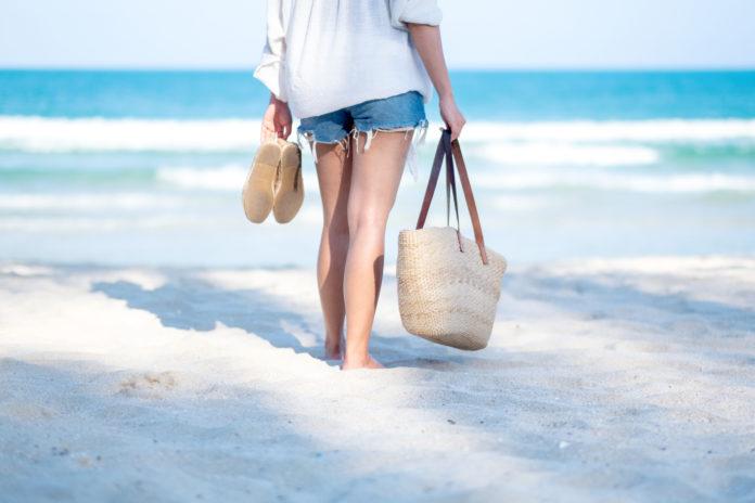 Kobieta na plaży z butami w dłoni