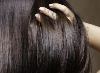 kobieta przeczesująca palcami włosy na tyle głowy
