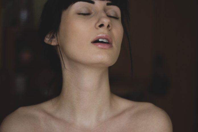 Kobieta z przymnkniętymi oczami i rozchylonymi ustami