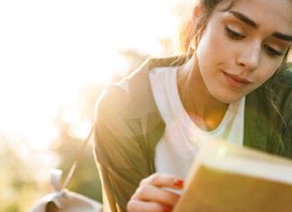 dziewczyna czytająca książkę na trawie
