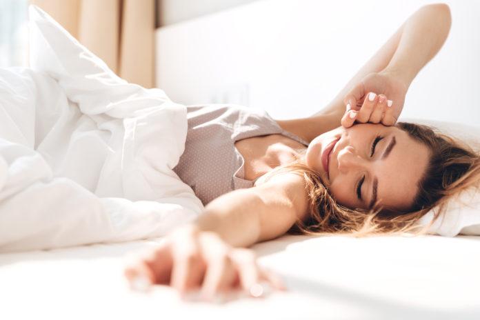 Kobieta przeciągająca się po przebudzeniu w łóżku