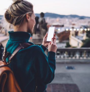 dziewczyna z plecakiem w podróży ze smartfonem