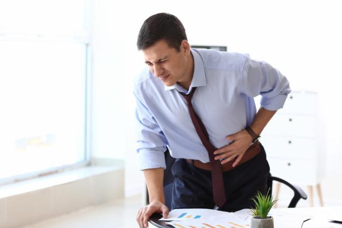 młody mężczyzna z bólem brzucha stojący przy biurku