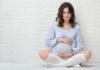 młoda kobieta w ciąży w błekitnej sukience i podkolanówkach