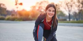 kobieta w stroju do biegania zawiązuje but