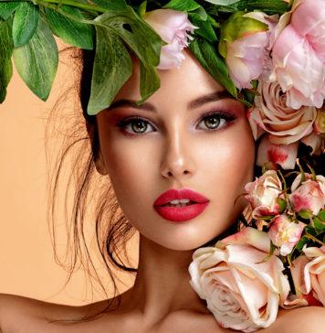 kobieta w pięknym makijażu z kwiatami przy twarzy