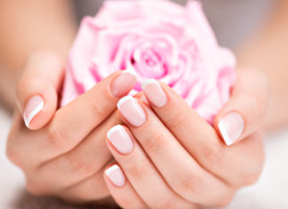 kobieta z zadbanymi paznokciami i dłońmi trzymająca różę w dłoniach