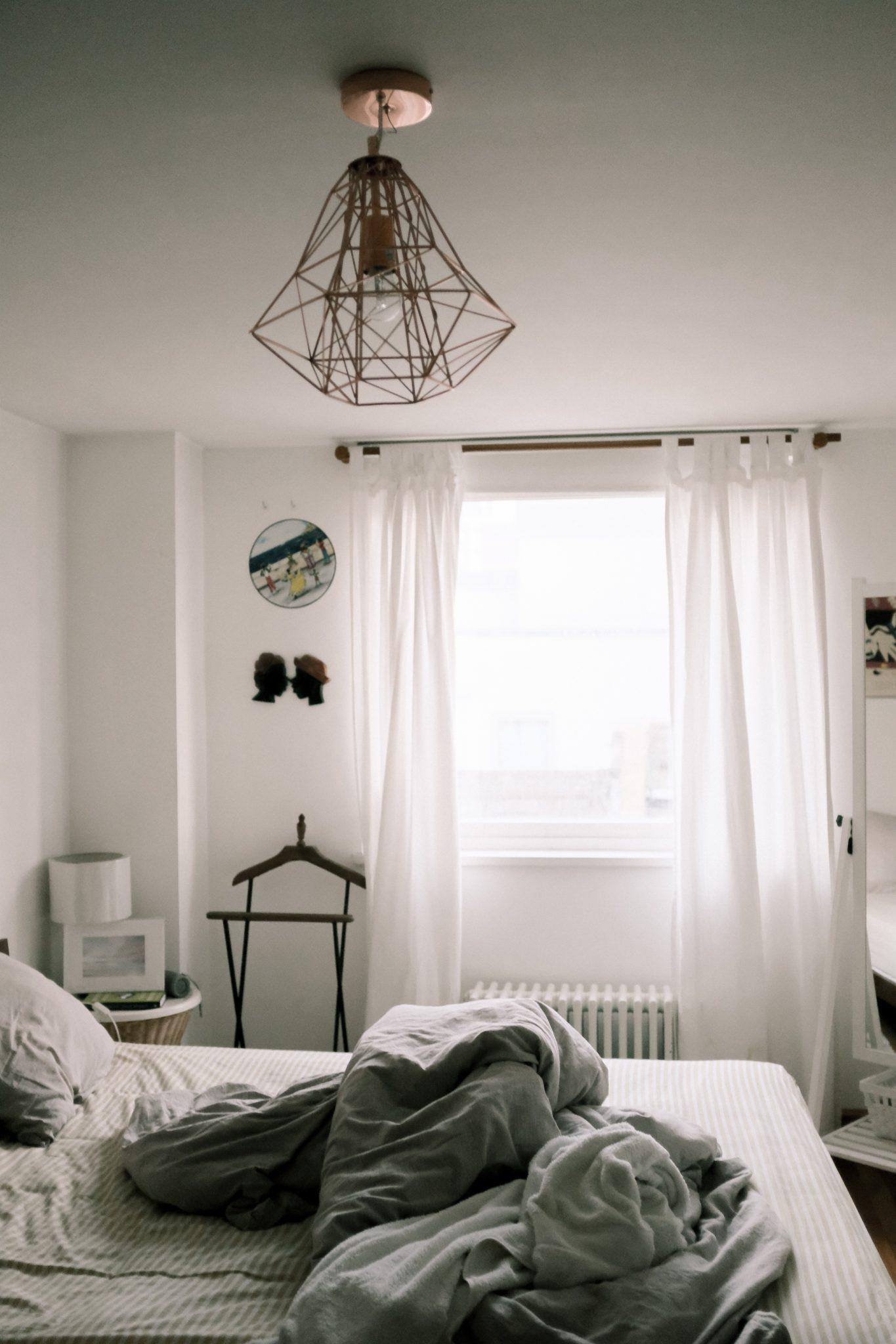 minimalistyczna sypialnia z efektownym żyrandolem