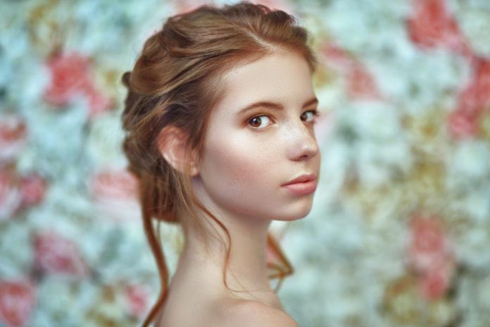 rudowłosa dziewczyna o alabastrowej skórze na kwiatowym tle