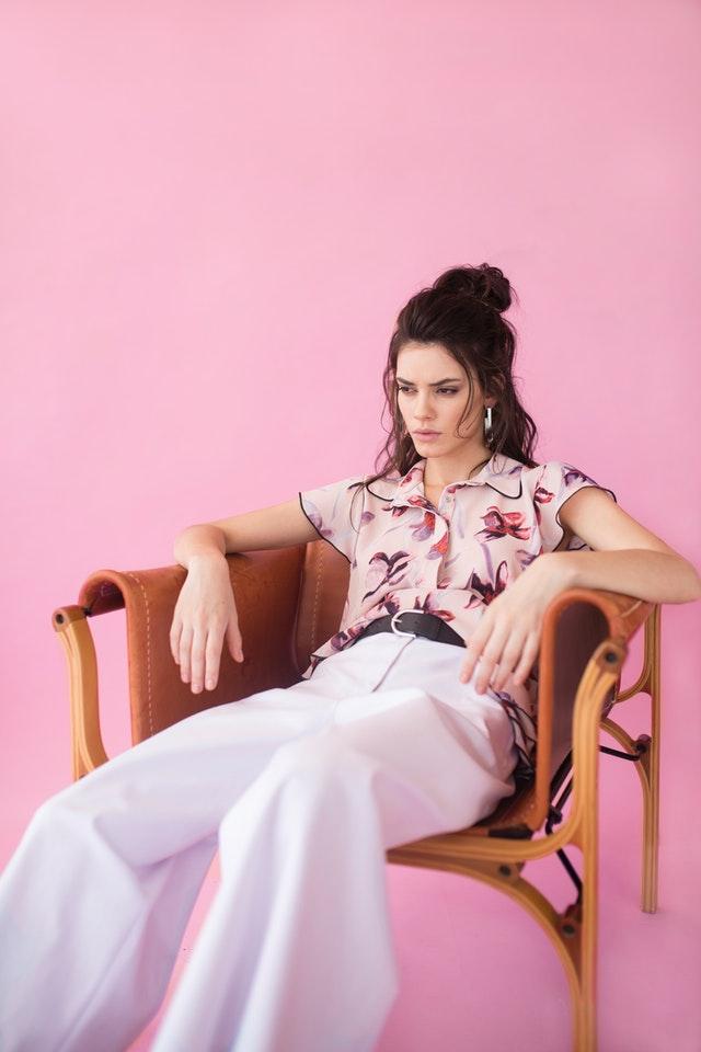 wysoka modna kobieta siedząca na krześle na różowym tle