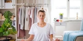 Młoda dziewczyna medytująca w domu na macie