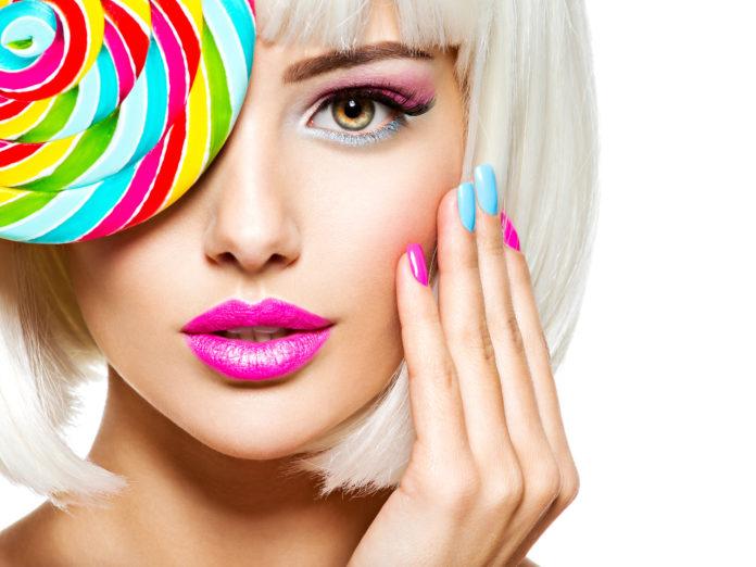 dziewczyna z kolorowym lizakiem w kolorowym makijażu z kolorowymi paznokciami