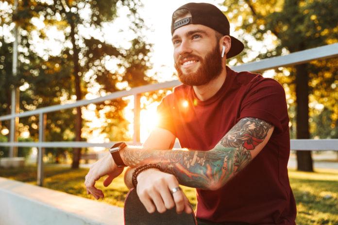 młody mężczyzna z tatuażami na rampie skate parku