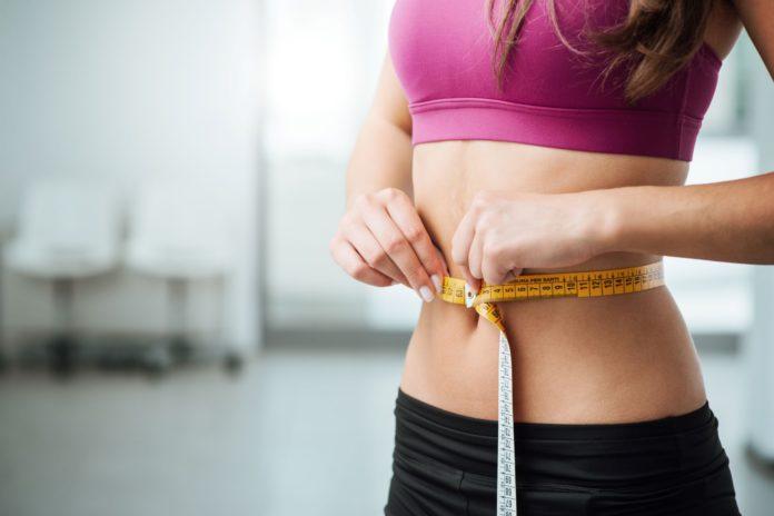kobieta z centymetrem na brzuchu