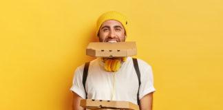 szczęśliwy mężczyzna na zółtym tle z opakowaniami pizzy jedno opakowanie trzyma w zębach