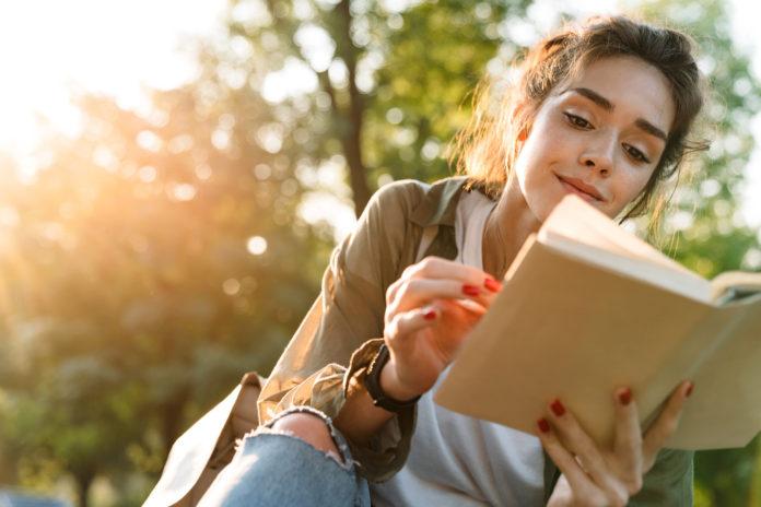 młoda dziewczyna czytająca książkę na zewnątrz