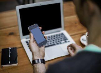 nowoczesna obsługa klienta mężczyzna przed laptopem ze smartfonem w dłoni