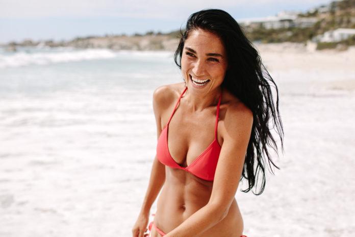 piękna szatynka z długimi włosami w bikini nad morzem