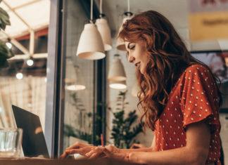 rudowłosa dziewczyna przy laptopie pisząca na blogu