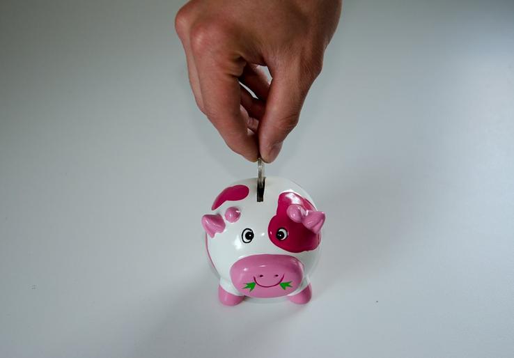 męska dłoń wkłądająca monetę do świnki skarbonki