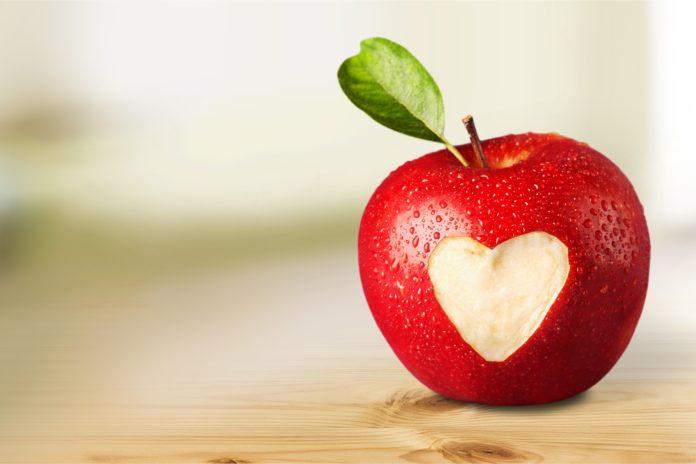 czerwone jabłko z wyciętym symbolem czerwonego serca