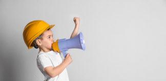 chłopiec w kasku z zabawkowym megafonem