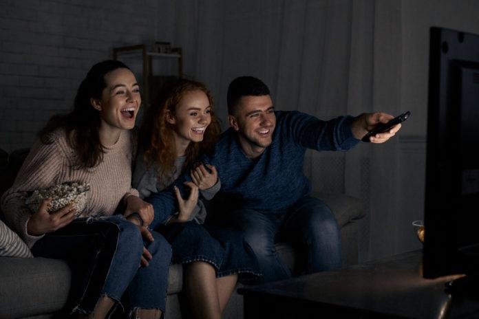 rozbawieni młodzi ludzie przed telewizorem