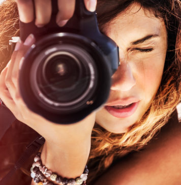 piękna kobieta z rozpuszczonymi włosami robiąca zdjęcia