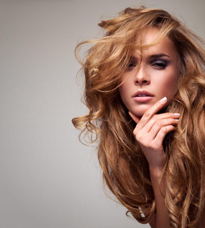 delikatna blondynka z długimi włosami z dłonią przy twarzy