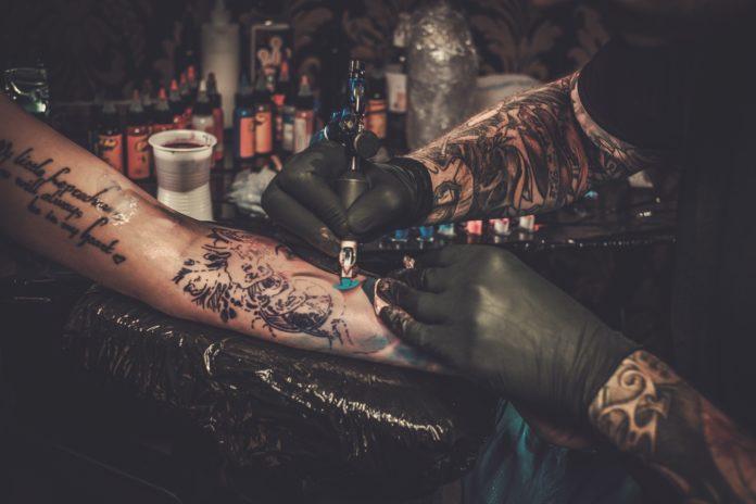 tatuażysta wykonujący tatuaż na kobiecej ręce
