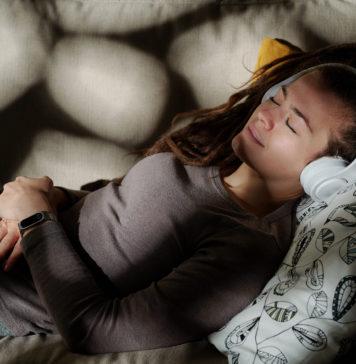 młoda kobieta śpiąca w słuchawkach na uszach