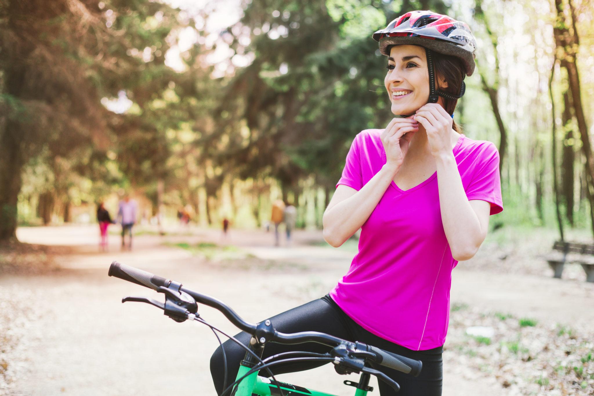 kobieta zakładająca kask rowerowy