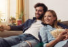 para oglądająca serial na kanapie w domu