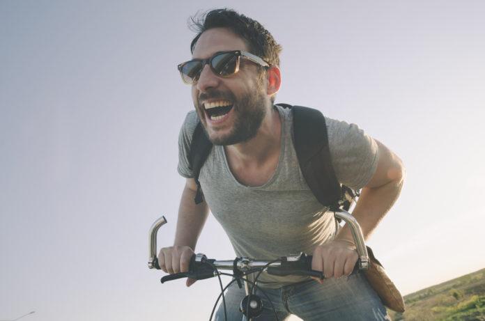 roześmiany mężczyzna na rowerze