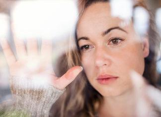 młoda smutna kobieta za szybą