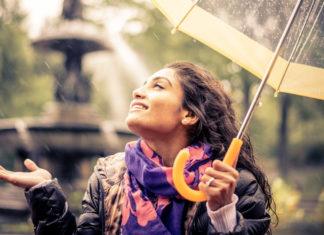 szczęśliwa kobieta pod parasolem w czasie deszczu