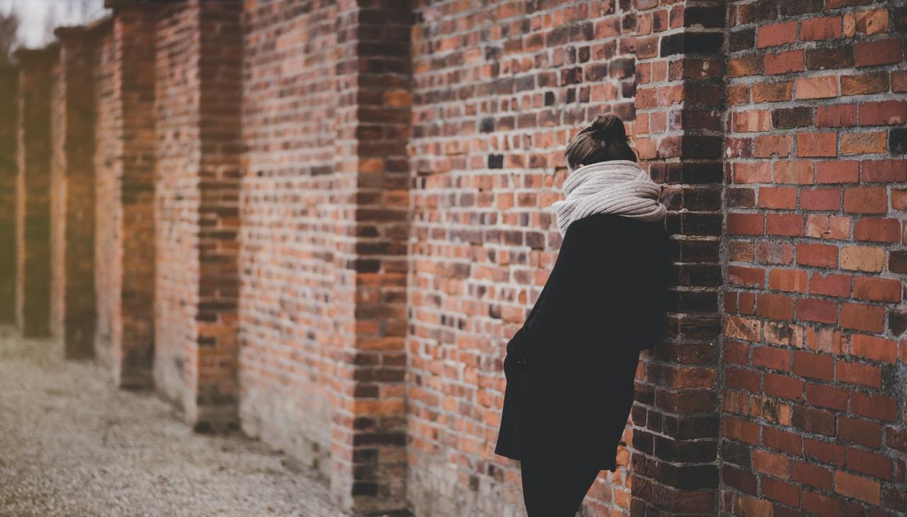 kobieta w czarnym płaszczu oparta o ścianę