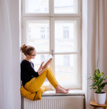 młoda kobieta czytająca w oknie