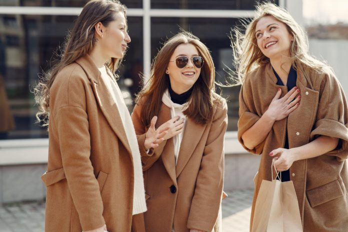 trzy kobiety w beżowych płaszczach