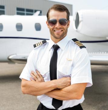 przystojny pilot na tle samolotu