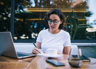 kobieta w kawiarni robiąca notatki w planerze